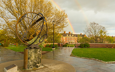 Double rainbow behind residence hall and sundial.