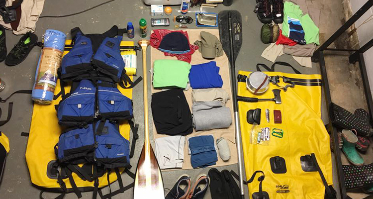 Canoeing gear spread out on the ground–life vests, clothes, a sleeping mat, sunblock, bug spray, paddles, an ax, sunglasses, watershoes, and more.