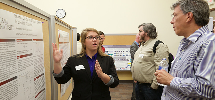 Female student presenting her poster presentation to another male student.