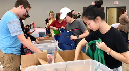 Students working to stuff bags full of school supplies for students.