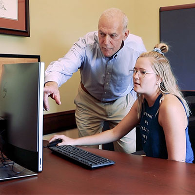 A student working with Ted Light, chair of the Commerce Department and Academic Advisor.