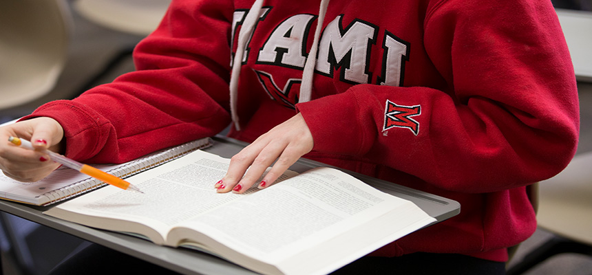Image of a textbook on a desk with a pencil in someones hand and a Miami red sweatshirt