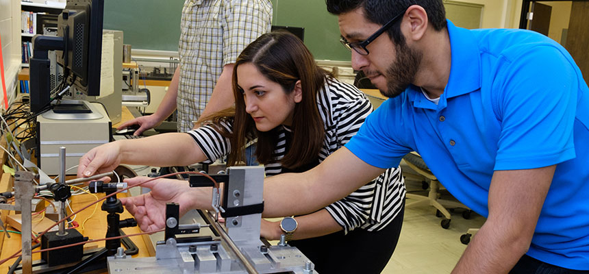 An ent student working with his professor and a piece of engineering equipment.