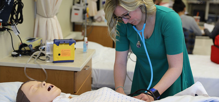 A female nursing student working on a simulation mannequin with a stethoscope in her ears