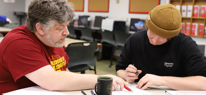 A student being tutored one-on-one while working on a piece of paper.