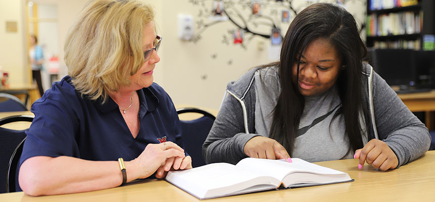 A tutor working with a student one-on-one in the tutoring and learning center.
