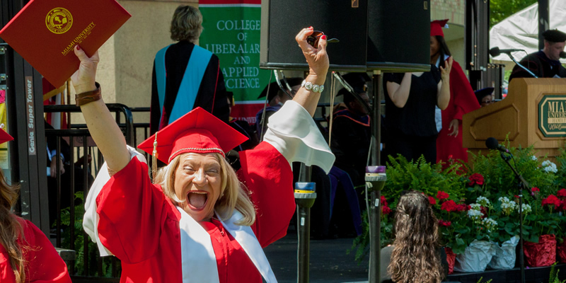 A TRIO grad with her hands up in the smiling after receiving her diploma.