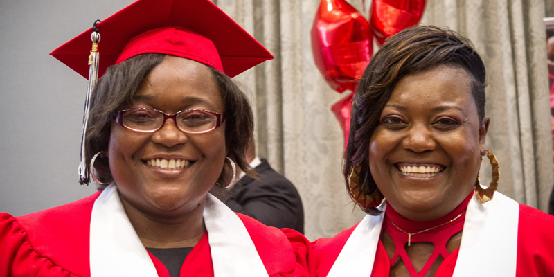 2 TRIO grads smiling at the camera in their graduation cap and gown.
