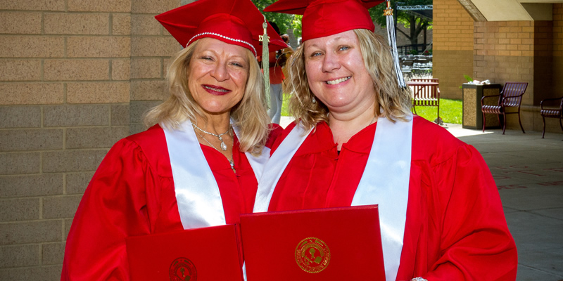 2 female TRIO grads smiling holding their diplomas with their arms around one another.
