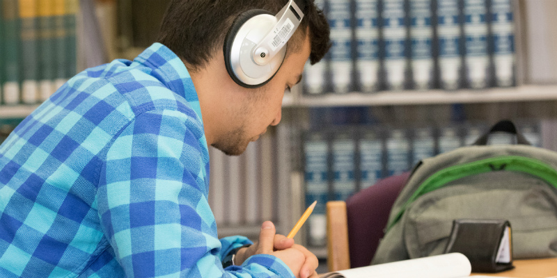 A student studying in the TRIO office with headphones on.