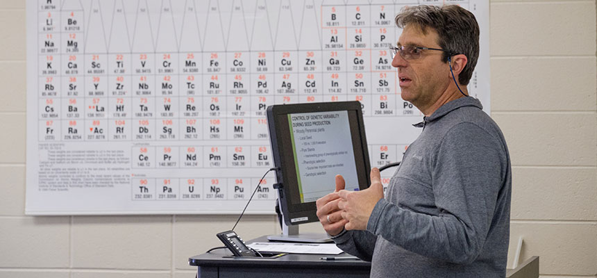 Brian Grubb standing in the front of the classroom teaching with a periodic table behind him.