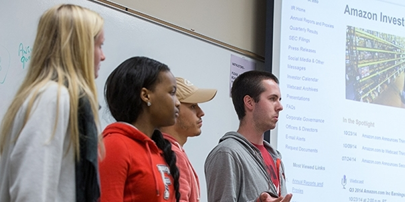 Students standing in a line in the front of the classroom giving a presentation.