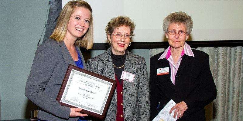 A female student poses with her award next to two women