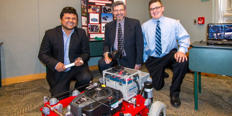 A senior design team poses with a wheeled project