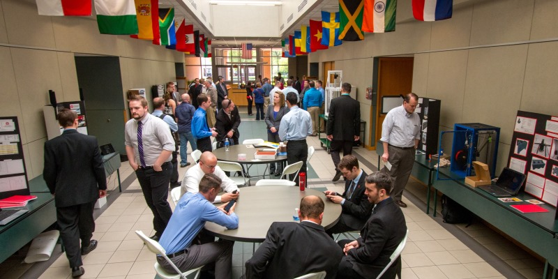 Hallway with students and visitors examining senior design project displays along the walls while others sit at round tables in the center of the aisle