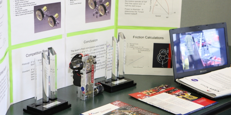 Detail of a student design project display board, including a laptop and devices on the table