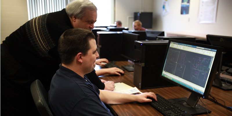 A student works at a computer in the computer lab while another man looks on