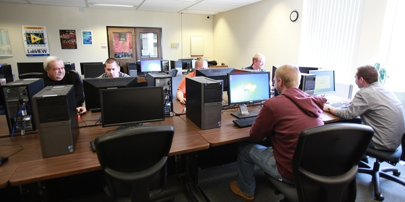 Several men work at computers in the computer lab