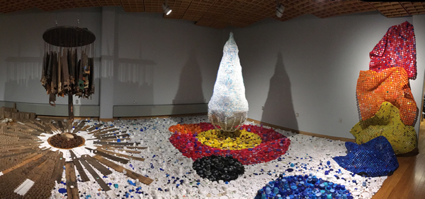 Environmental installation in studio, consisting of sculptures made from recycled materials such as brightly colored plastic bottle caps, wood pieces and suspended handsaws.