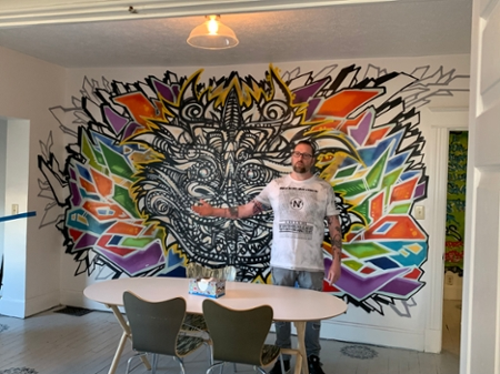A man standing in front of a hand painted mural on the wall.