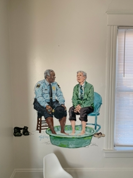 A hand painted mural of a police officer sitting with another person with their feet in a small kiddie pool.
