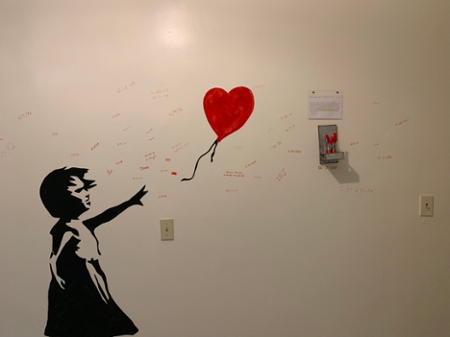 A painting of a silhouette of a girl chasing a red balloon.