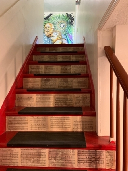 The staircase at The Fringe Coffee House with pages from books lining the bottom on the stairs.