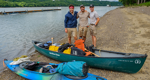 Quentin Couch, Jackson Gray and Tyler Brezina stand on shore behind their packed canoe and kayak.