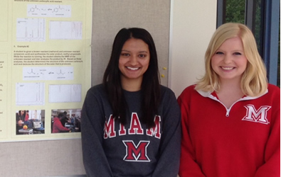 Students Abby and Meena stand in front of the poster that explains their undergraduate research project.