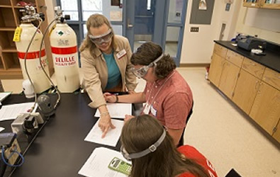 Dr. Susan Marine works in lab with two students.