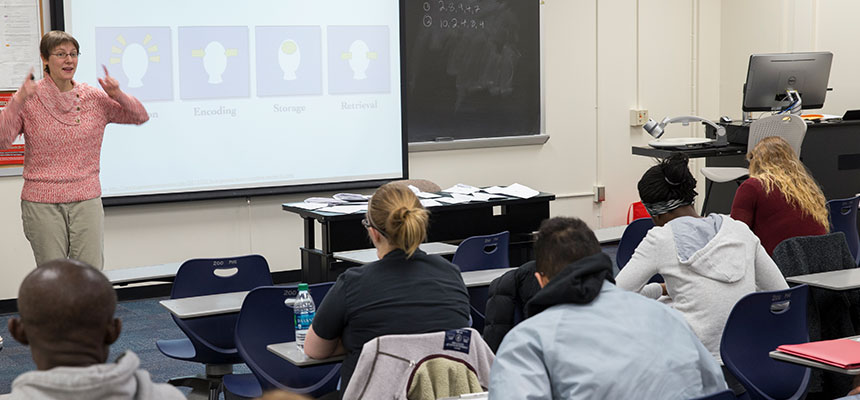 A female professor standing in the front of a classroom of students next to the projector screen.