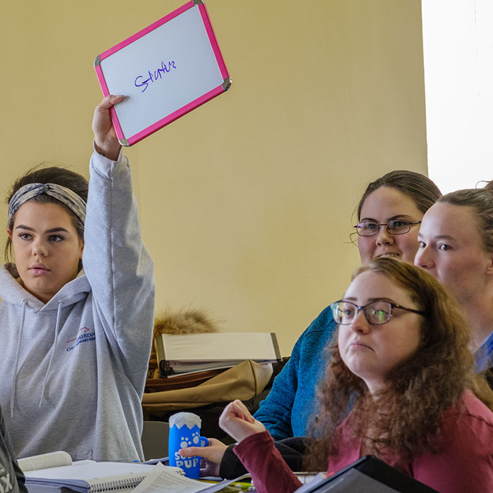 A group of female students sitting around a table with one of them holding up a small whiteboard that reads structure.
