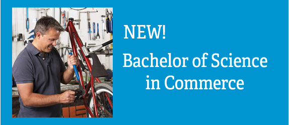 Small business owner working in his cycle shop. Text: New: Bachelor's of Science in Commerce