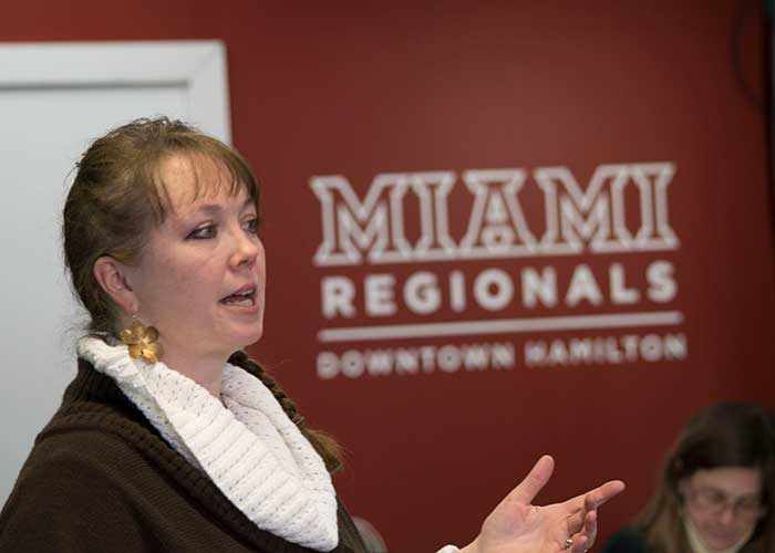 A woman standing up speaking with the Miami Regionals Hamilton Downtown wordmark on the wall in the background