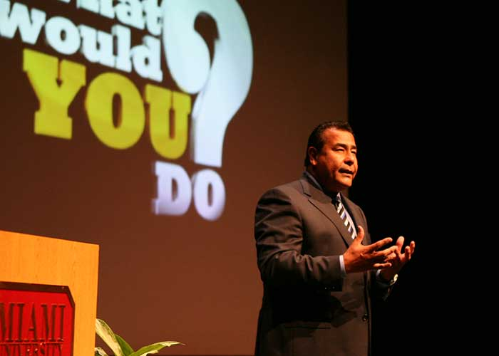 John Quiñones speaking on the stage in the Harry T. Wilks Conference Center at Miami Hamilton.