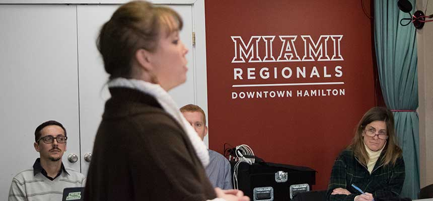A woman speaking with the Miami Hamilton Downtown wordmark on the wall in the background.