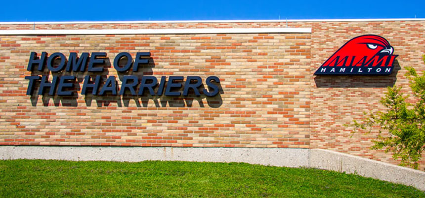 The exterior of the gymnasium with a sign that reads Home of the Harriers and the Miami Hamilton Harriers logo