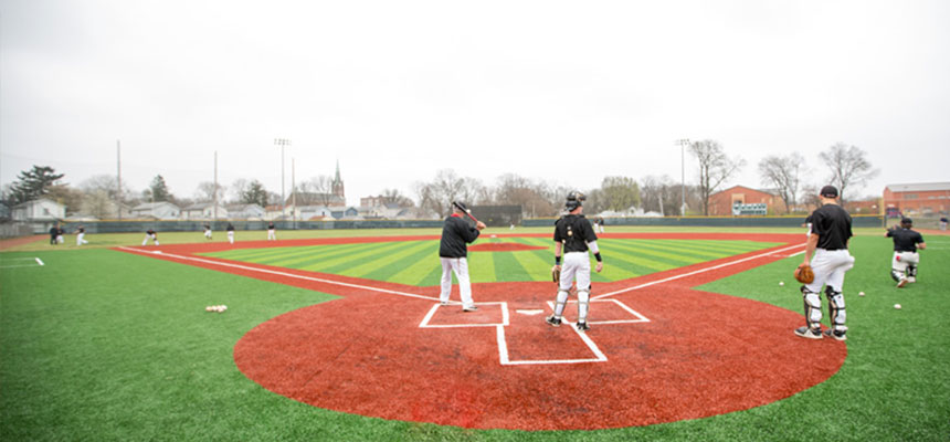 Harrier Baseball players taking infield during a game.