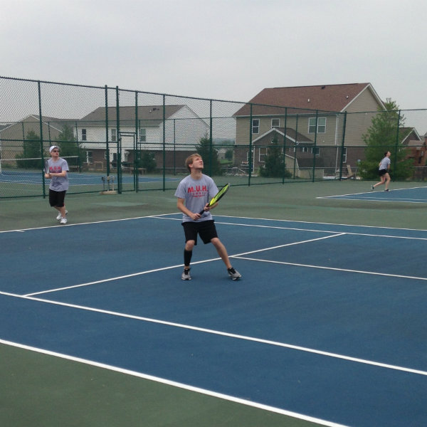 Mens Doubles team returning a serve