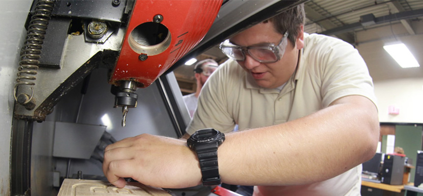 A male student working on a piece of engineering equipment