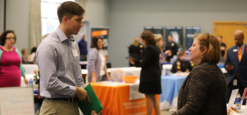 Male student speaking to female at career fair