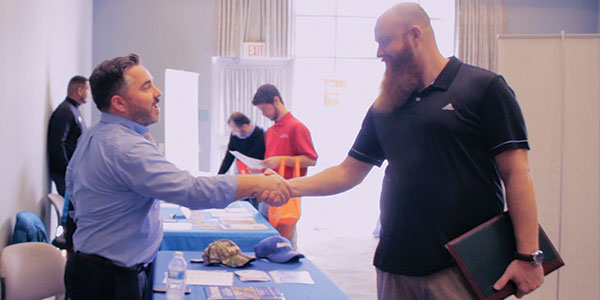 A male shaking another males hand at the career and internship fair