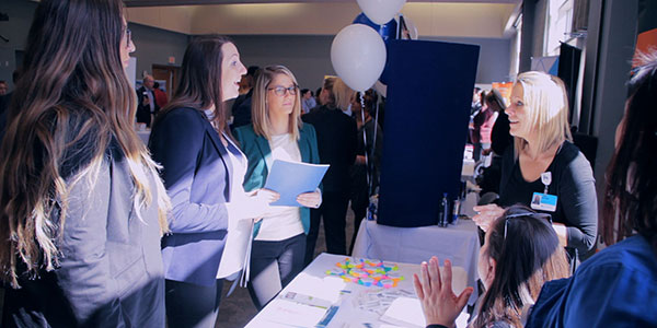 Three female students talking to a female employer at a booth during the 2017 Career and Internship Fair