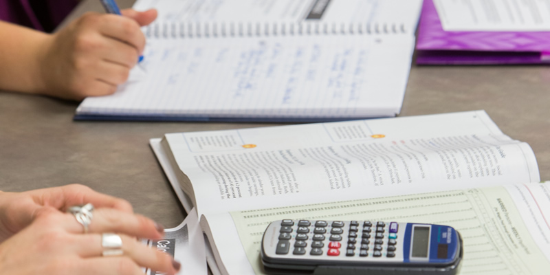 Close up of textbook and calculator
