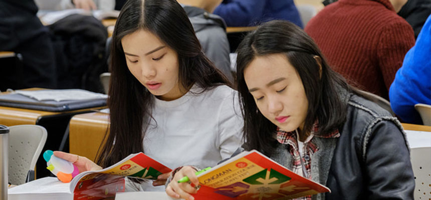 2 female international students sitting at their desks reading their books