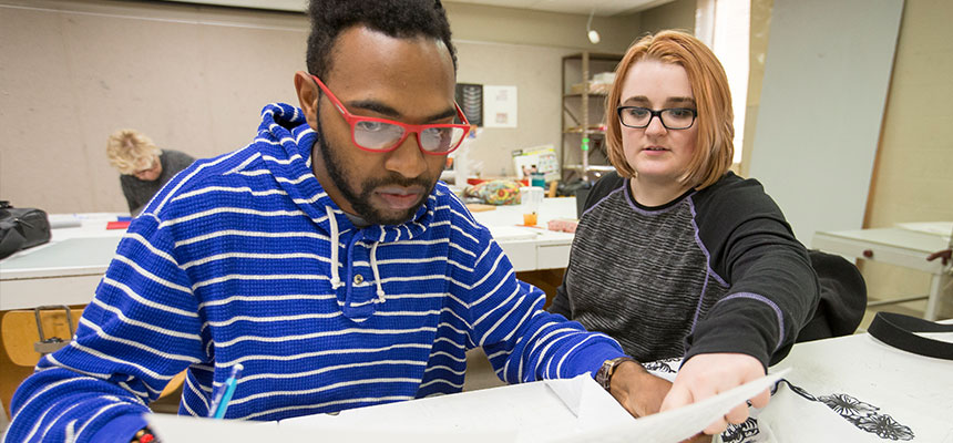 A female and a male student sitting looking at a piece of paper during a printmaking class