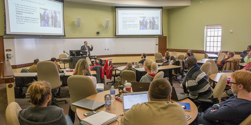 JCS professor addresses class in large classroom at VOALC