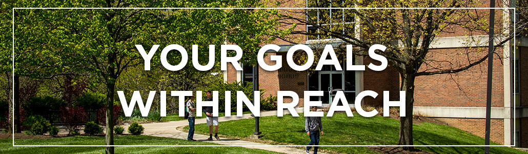 Your Goals Within Reach. Students walking on the sidewalk with Thesken Hall in the background.