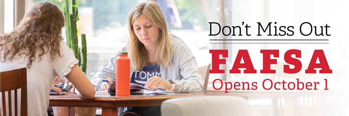 Don't Miss Out. FAFSA Opens Oct. 1. Students sitting at a table studying across from one another.