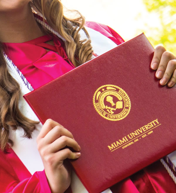 Graduate holding Miami University diploma case.